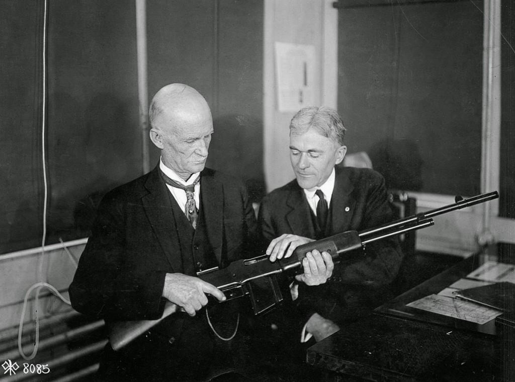 Двое мужчиносматривают ружьё