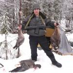 Охотник держит гусей за шею