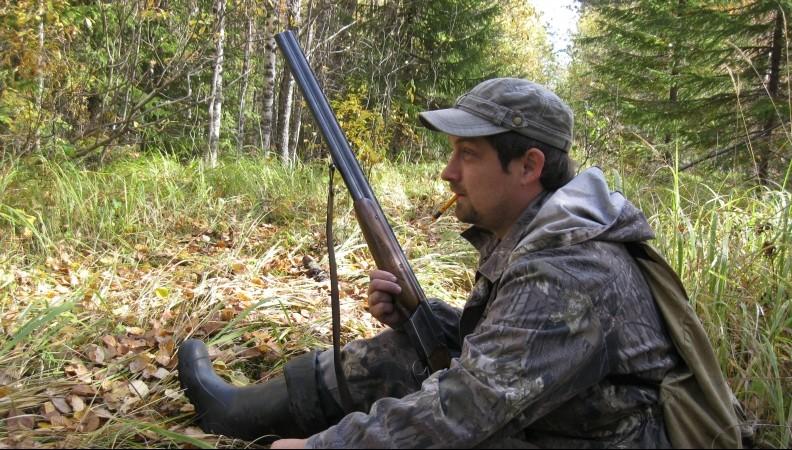 Охотник с ружьем сидит
