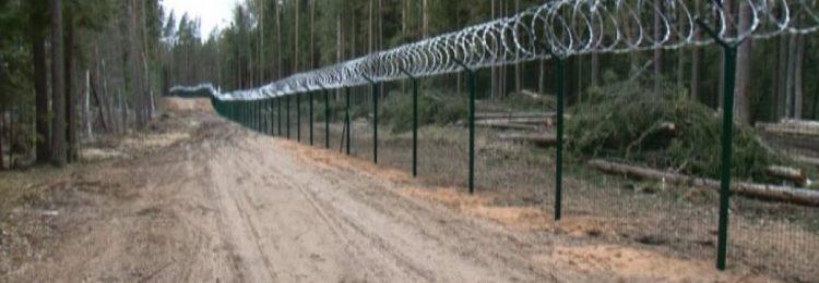 Длинный забор с колючей проволокой