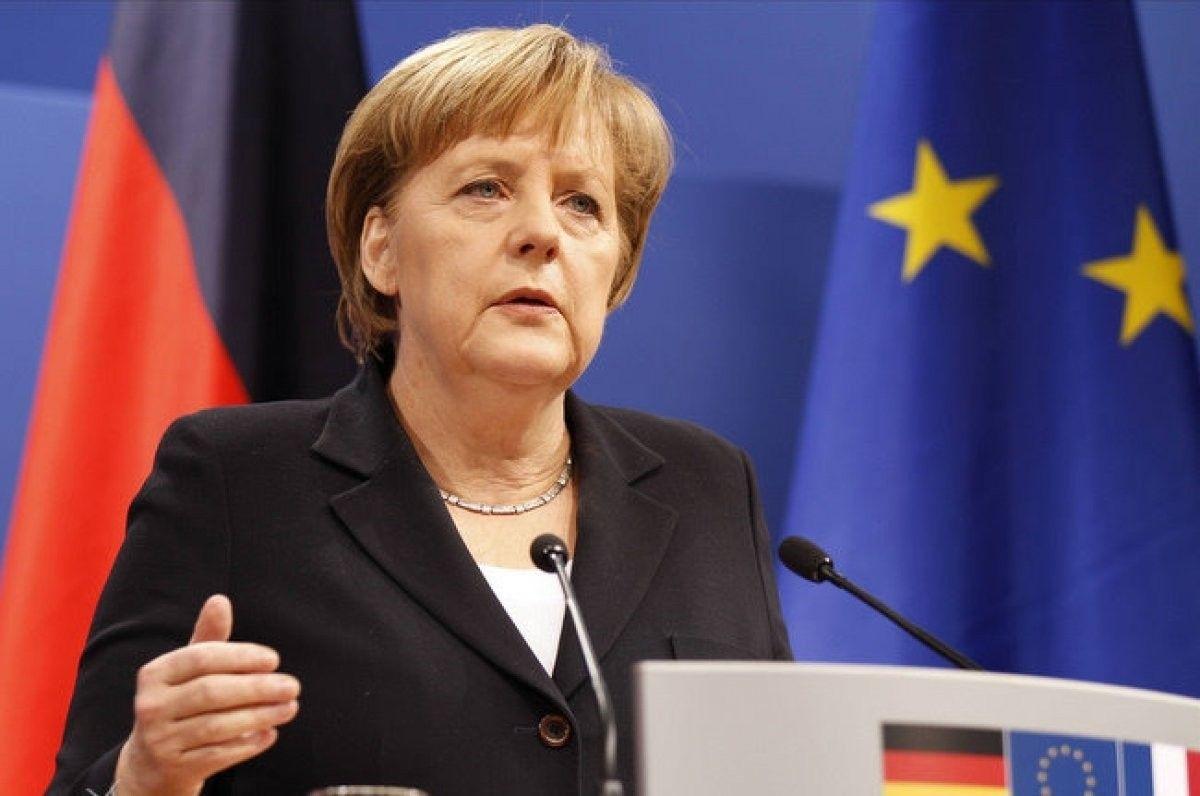 Меркель у флагов Германии и ЕС