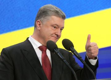 Порошенко стоит на фоне украинского флага