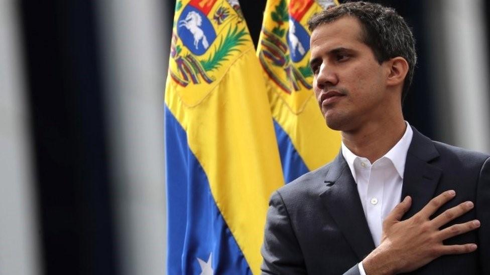Гуайдо на фоне флага Венесуэлы