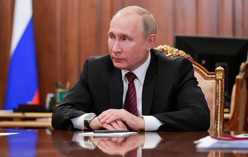 Путин сидит за столом