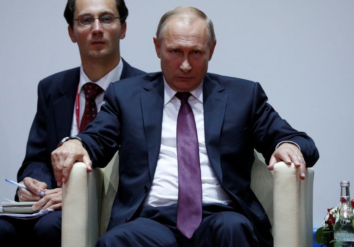 Путин сидит в кресле, как на троне